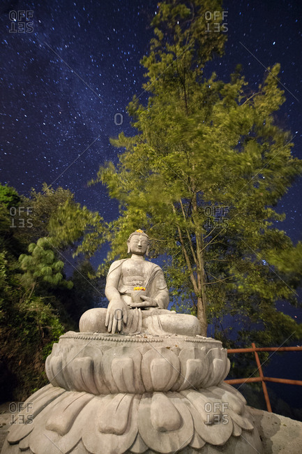 Night sky above a Buddha statue sitting in Lotus Position.