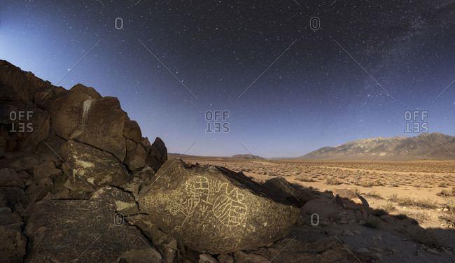 Night sky in a moonlit night above an ancient Native American petroglyph in the Owens Valley of Sierras, California.