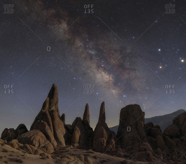 Bright galactic core of the Milky Way with Mars, Saturn, and Antares in Scorpius above moonlit sandstone rock formations in the Alabama Hills of California.
