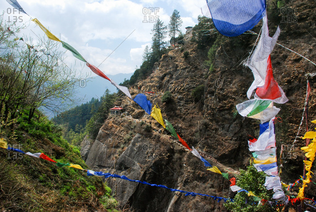Prayer flags line the hiking path leading to Taktsang Lhakhang, known as The Tiger's Nest, which is a monastery clinging to a vertical granite cliff.