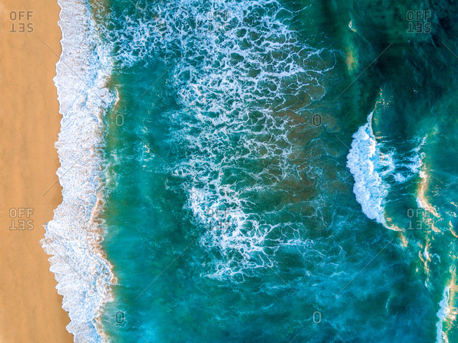 An aerial view of waves crashing against the Baja coastline.