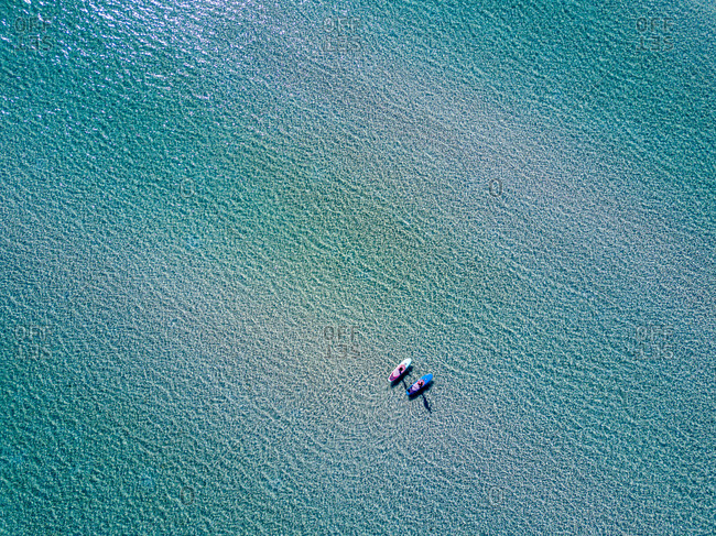 Two paddleboarders in Ballandra Bay as seen from the air.
