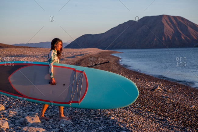 A woman carrying her paddleboard to the ocean on a remote beach on the Baja peninsula at sunrise.