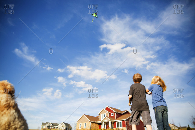 Low angle view of two children flying a kite