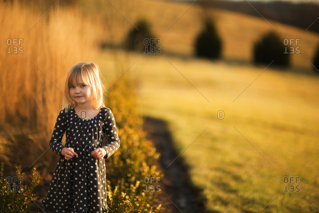 Little girl in field at sunset