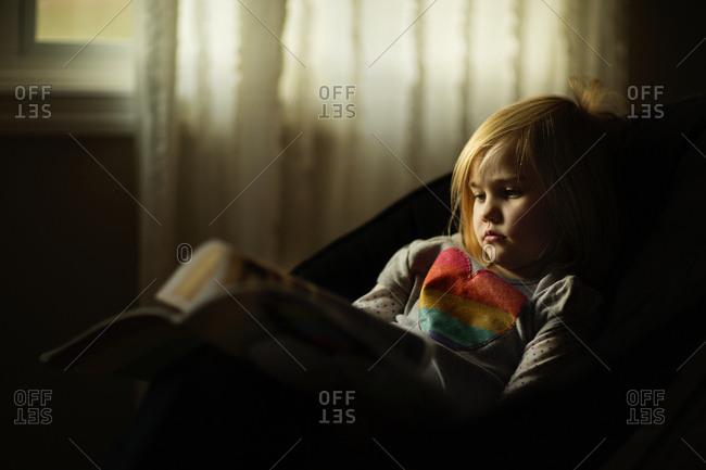 Preschool aged girl reading by window