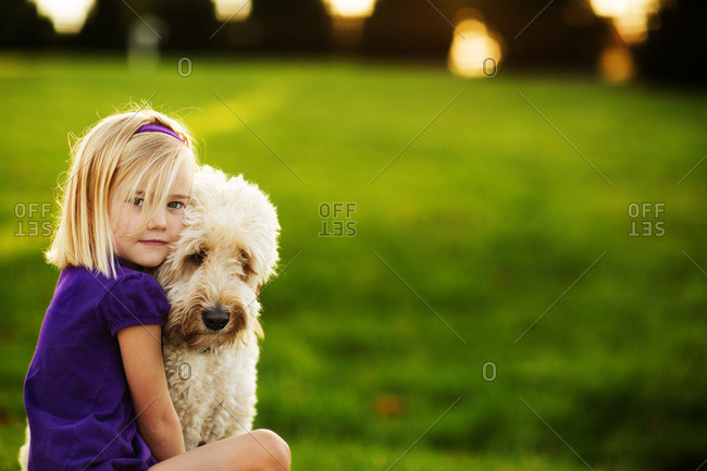 Portrait of girl with her labradoodle in grass