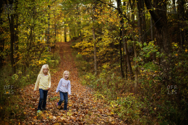 Two young sisters walking in forest in autumn