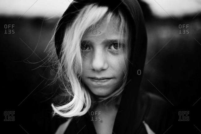 Girl wearing hood with curl of her hair peeking out