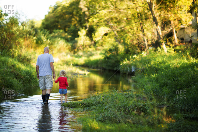 Man with daughter wading in stream