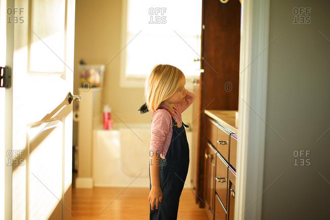 Preschool aged girl brushing her hair in bathroom