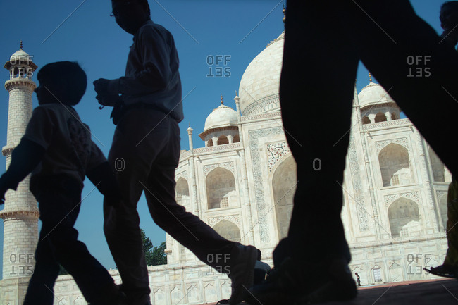 Agra, India - September 15, 2009: Seeking shade from the burning sun, the photographer's vantage point captures people passing in front of the Taj Mahal