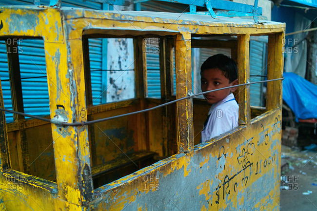 Delhi, India  - September 15, 2009: Young child riding to school in a rickshaw