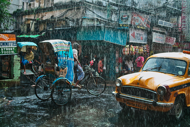 Kolkata, India - September 25, 2009: Dramatic street scene in a shopping district as rain pours down during Monsoon season