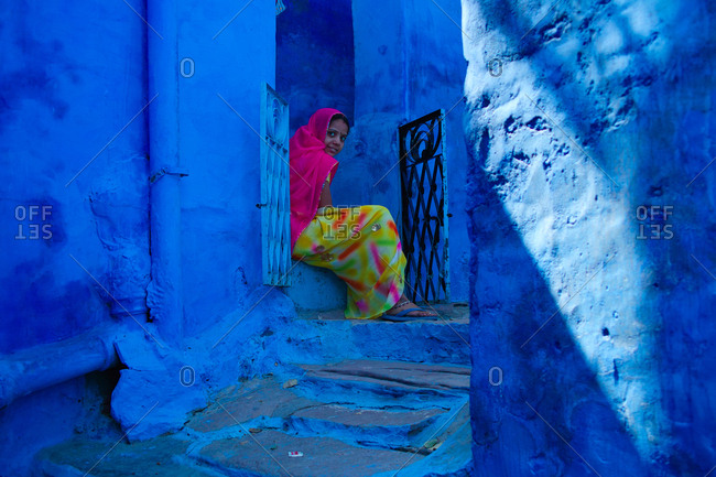 Jodhpur, India - September 15, 2009: Young woman sitting in an alley near the Mehrangarh Fort