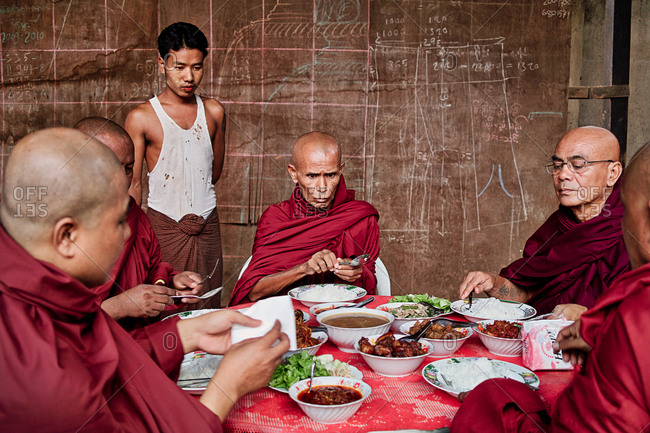 Mandalay, Myanmar - September 15, 2009: Buddhist monks gathered around a table for a meal