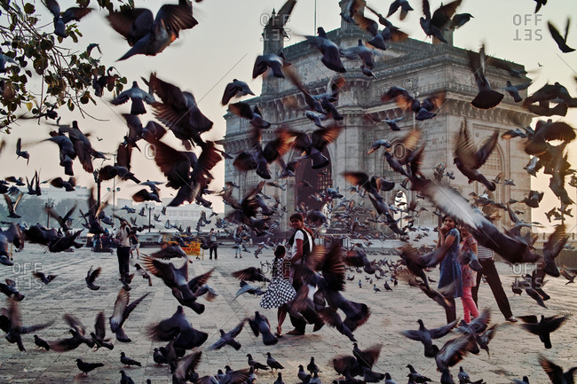 Mumbai City, India - September 15, 2009: Tourists in front of The Gateway, seen through a flock of birds in mid flight