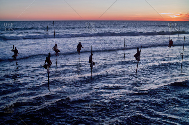 Stilt fishermen at dusk