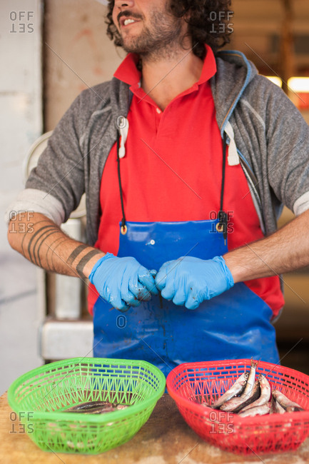 Syracuse, Italy - July 22, 2015: Man cleaning sardines in a fish market