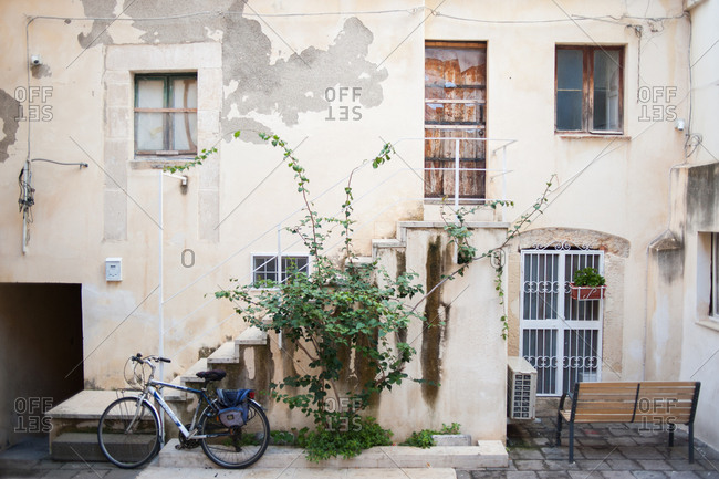 Building exterior with stairs and a bike in Syracuse, Italy