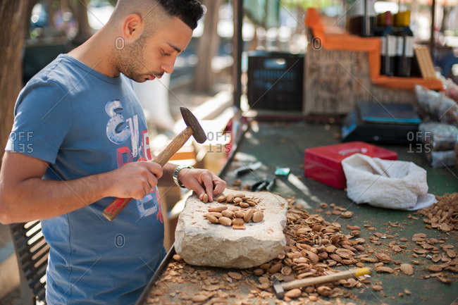 Marzamemi, Italy - July 22, 2015: Man cracking nuts with a hammer and stone