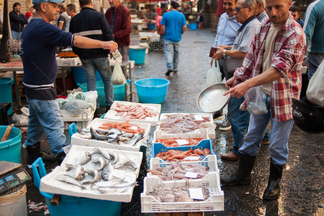 Catania, Italy - July 22, 2015: Man selecting fish in a busy fish market in Catania, Italy