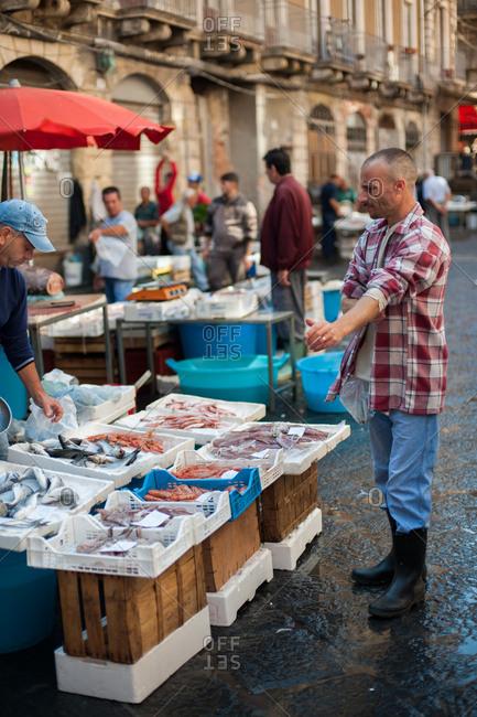 Catania, Italy - July 22, 2015: Man choosing fish in a busy fish market in Catania, Italy