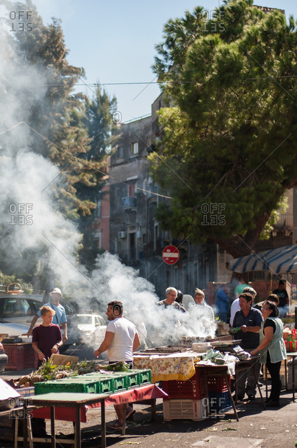 Catania, Italy - July 22, 2015: Vendors grilling vegetables at a farmer's market in Catania, Italy