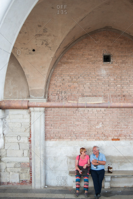 Venice, Italy - July 22, 2015: Couple sitting on a bench at Doge's Palace in Venice