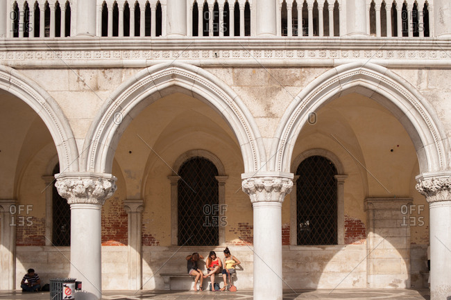 Venice, Italy - July 22, 2015: Women sitting on a bench at Doge's Palace in Venice