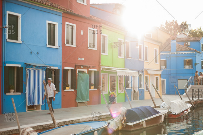 Venice, Italy - July 22, 2015: Colorful buildings and boats in a canal in Burano, Venice, Italy