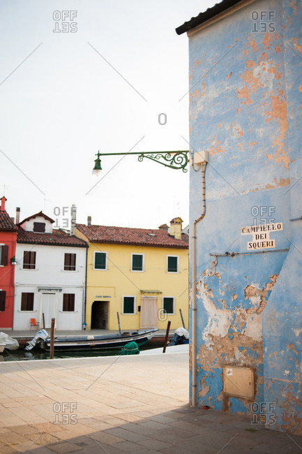 Old blue building by the canal in Burano, Venice, Italy