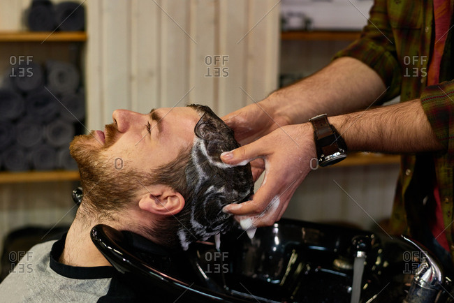 At hairdresser salon. Close-up view of male barber washing head of middle-aged bearded customer above black sink