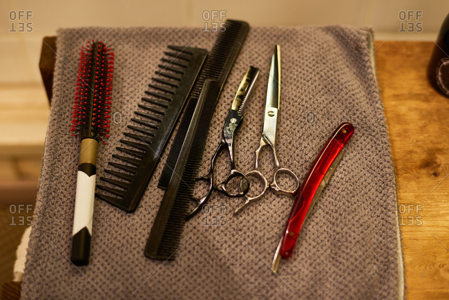 Tools of hairdresser. Close-up view of metal scissors, plastic black combs and old-fashioned razor lying on towel in barbershop
