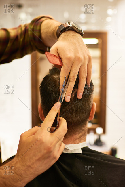 Getting haircut in salon. Rear view of hairdresser hands trimming wet hair of male customer with scissors and comb