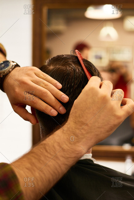 Getting new haircut. Hairdresser combing wet hair of male customer sitting in front of mirror in barbershop, rear view