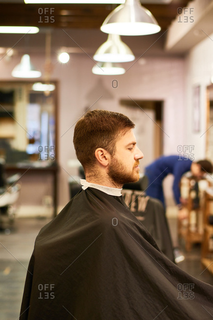 At barbershop. Side view of middle-aged bearded man sitting in salon in black barber cape and waiting for hairdresser