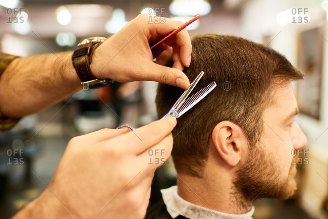 In barbershop. Close-up view of hairdresser hands holding metal scissors and trimming hair of male bearded customer