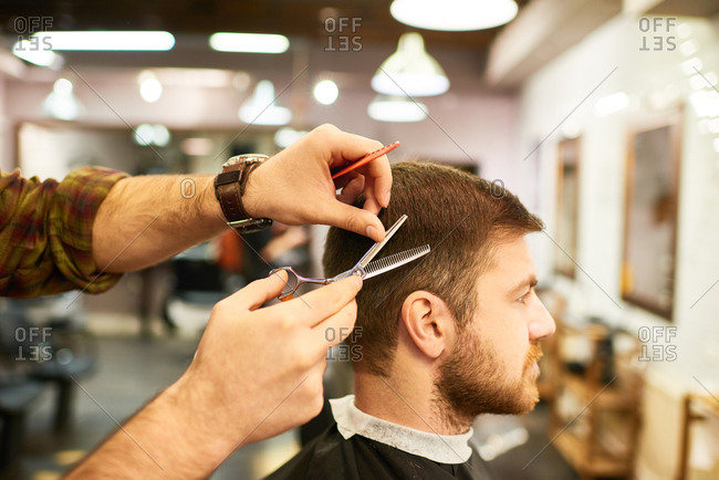 Side view of middle-aged bearded man getting stylish haircut with scissors by male hairdresser in professional barbershop