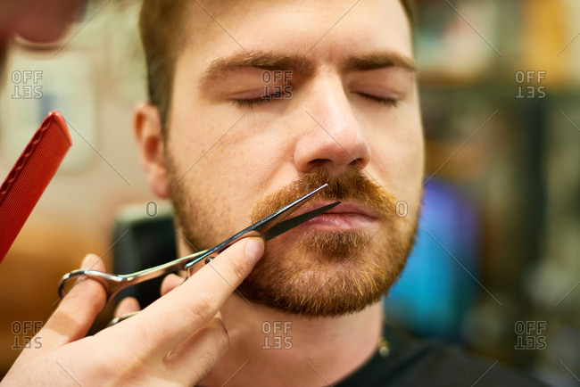 Close-up view of middle-aged bearded man sitting with his eyes closed while professional barber trimming his moustache with scissors carefully