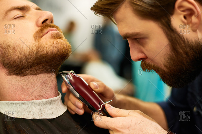 Dry shaving in barbershop. Close-up shot of concentrated bearded barber shaving neck of male client with electric razor