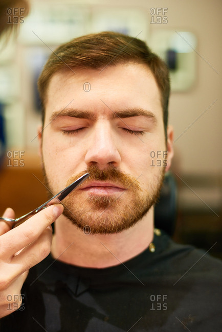 Close-up portrait of young bearded man sitting at barbershop with his eyes closed while master trimming his moustache with grooming scissors