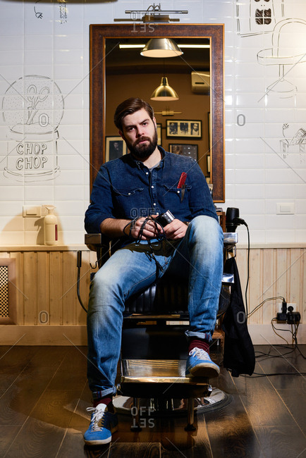 Portrait of confident bearded hairdresser in denim wear sitting in barber chair with electric hair clipper