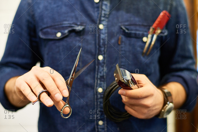 Close-up shot of male hairdresser in denim shirt holding professional grooming scissors and old-fashioned electric hair clipper in barbershop
