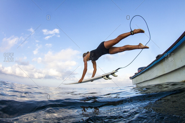 Indonesia - September 1, 2013: A surfer jumps out of the boat in remote Indonesia