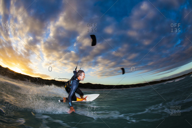 Australia - March 15, 2011: A kite surfer against a colorful cloudscape in western Australia