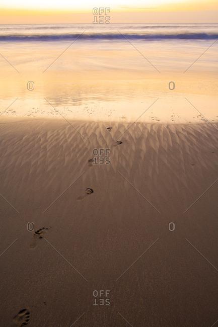 Footsteps lead to the ocean in northern Peru
