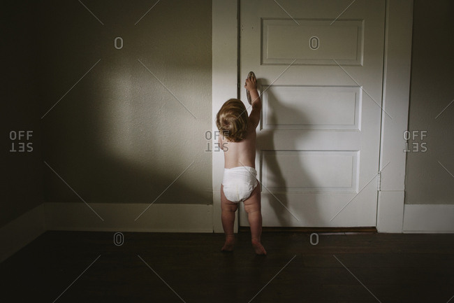 Baby in diaper reaching to open door