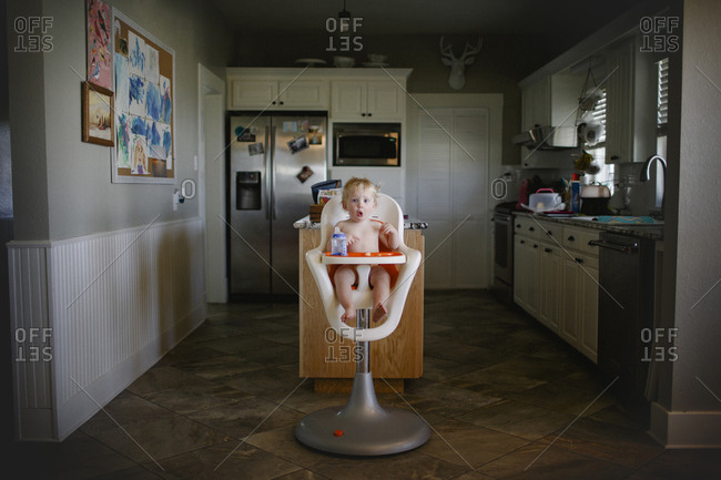 Boy sitting in high chair making funny face