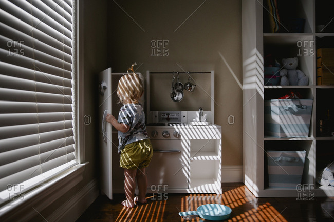 Toddler cooking in play kitchen surrounded by dappled light